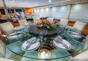 large round glass table in the indoor dining area of luxury yacht island heiress