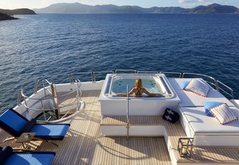 superyacht jacuzzi with charter guest lying back enjoying the sun