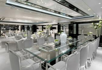 glass-topped table in formal dining area in main salon aboard charter yacht Silver Angel