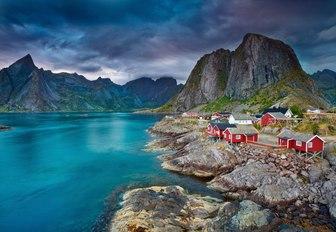 sun sets behind a village in the Lofoten Islands, Norway