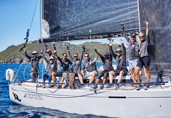 sailors competing at Les Voiles de Saint Barth celebrate as the cross the finish line