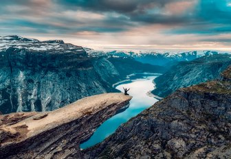 hiker sits on edge of Trolltunga Mountain in the Norwegian Fjords