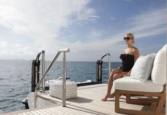 charter guest hangs out on the swim platform of motor yacht Lady E