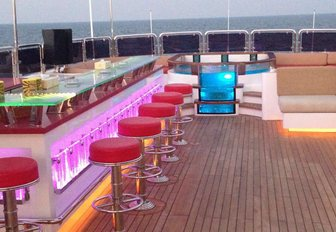 bar and Jacuzzi on the sundeck of superyacht Code 8 light up as the sun begins to set