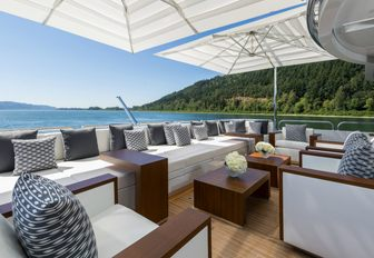 sundeck of luxury yacht chasseur, with seating area and parasols