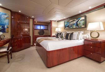 master suite decorated in rich woods aboard charter yacht Sweet Escape