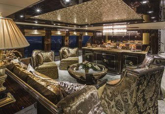opulent main salon with gold-coloured seating on board motor yacht 'Lady Bee'