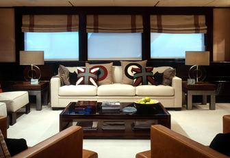 Comfortable interior of Illusion I yacht with windows behind and comfortable sofa
