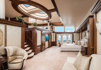 master suite with bed, skylight, seating areas and stairs to an upper level on board charter yacht CALYPSO