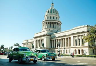 vintage cars drive past the Capitol building in Havana, the capital of Havana