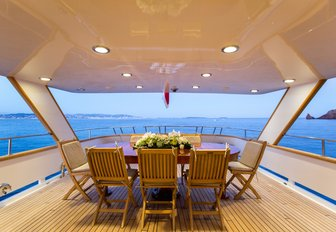 alfresco dining setup on aft deck of charter yacht LIBERTUS