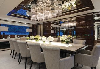 formal dining table sits under a chandelier in the main salon of luxury yacht 11/11