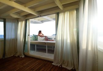 charter guest reclines in master suite's master suite aboard luxury yacht ALEXA
