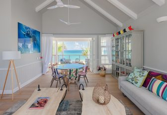 entertainment room on villas of thanda island, with balcony overlooking the sea and sofa in foreground