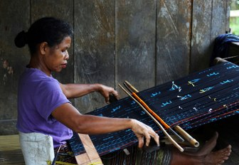 local Ngada woman hand-crafting ikat weavings