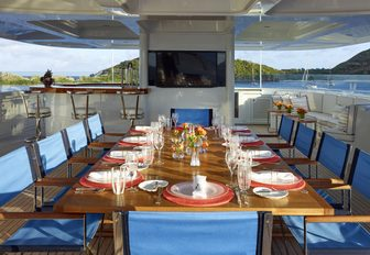 long dining arrangement on luxury yacht, with tv screens mounted on wall
