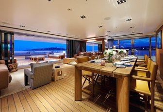 teak-floored dining area on board superyacht Planet Nine