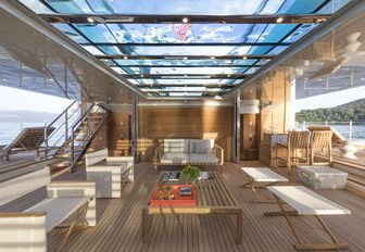 A glass encased swimming pool forms the ceiling of a superyacht beach club