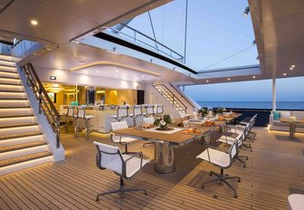 dining and indoor-outdoor bar on aft deck of superyacht AQUIJO