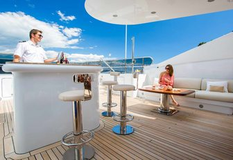 charter guests enjoys drink from the sundeck bar aboard luxury yacht DIANE