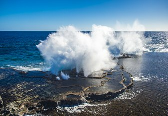 Powerful waves crashing into the reef, the famous Mapu'a 'a Vaea blowholes in Tonga