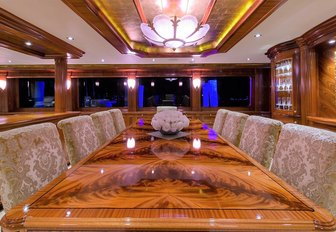 rich wooden dining table in the main salon aboard charter yacht EXCELLENCE