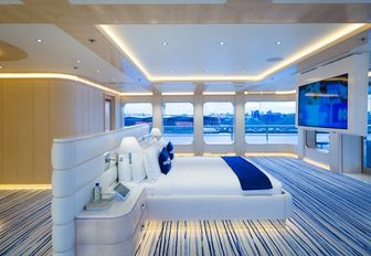 the bright and airy master stateroom in charter yacht aquarius with blue and golden accents throughout