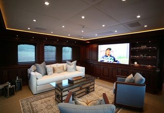 the classically styled upper loung with flat screen tv, bookshelf and luxurious seating inside charter yacht clarit