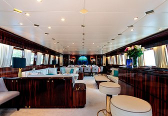 Main salon on board superyacht HEMILEA, with dining in background and bar with fresh flowers on it in foreground