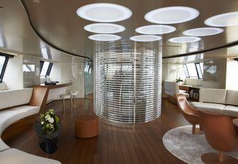 main salon of luxury charter yacht panthalassa with staircase and lighting panels overhead