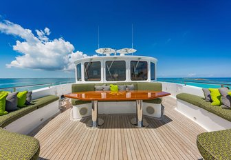 the spacious and grand sun deck of charter yacht gota with green accents, sumptuous loungers, overlooking the clear blue sky of the mediterannean