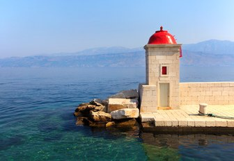 Small church with scarlet dome overlooking the clear water in Croatia