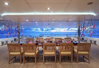 large al fresco dining area on board charter yacht TITANIA at twilight