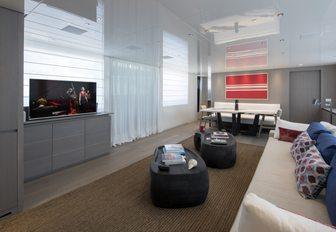 long sofa faces TV in the main salon of luxury yacht Dinaia