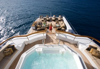 the spacious and glamorous main and upper aft decks of charter yacht utopia with a woman ascending the stairs from the spacious beach club to the jacuzzi