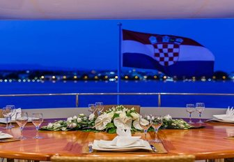 croatian flag on back of superyacht with dining in background