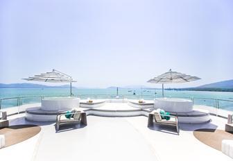 two Jacuzzis surrounded by sunpads on the sundeck of luxury yacht SALUZI