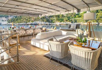 al fresco dining area and luxe seating area on the sundeck of luxury yacht Zulu
