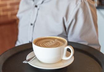 Man holds tray with latte on it at Boroughs in Yas Island, Abu Dhabi