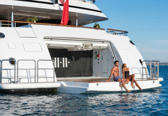 charter guests perch on edge of the drop-down swim platform aboard charter yacht 11/11