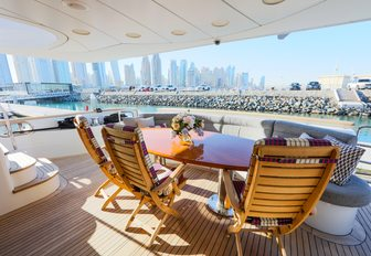 al fresco dining area on the main deck aft aboard superyacht with Dubai cityscape in the background