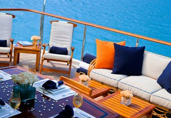 outdoor seating area with sofa, teak chairs and coffee tables on board motor yacht M4