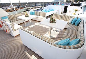 Twin alfresco seating spaces on superyacht HEMILEA, with wraparound sofas and elegant cocktail tables