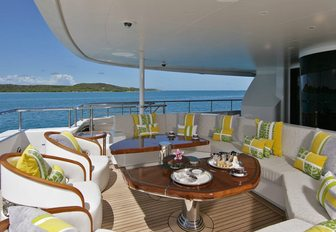 Aft deck onboard AMARYLLIS, white sofas and armchairs surround tables, surrounded by sea and distant islands.