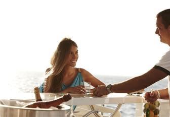 charter guest enjoys champagne in alfresco lounge aboard motor yacht E&E
