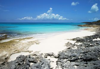 white sand deserted beach in the Bahamas with turquoise sea