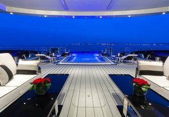 alfresco lounge looking over pool at night on board superyacht OKTO