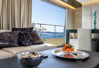 Fruit and snacks in bowls on table with sofa and large window in background of motor yacht Cinquanta 50