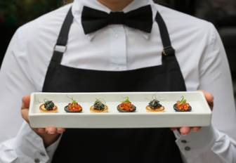 Man in catering uniform holding plate of small appetizers