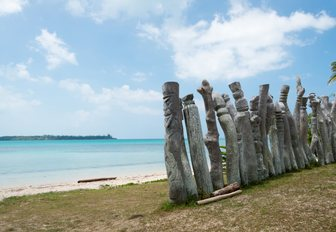 Old wooden guardians on the beach of the Saint Maurice Bay on the Pines Island in New Caledonia